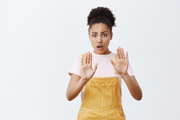 Kalmeren, pistool neerleggen. intens bezorgde en nerveuze bange afro-amerikaanse vrouw met krullend haar in gele overall, handpalmen omhoog, vragen om te ontspannen en te chillen, troost proberen depressieve vriend