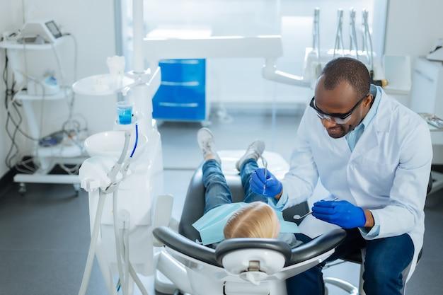 Kalmerende kind. aangename, vrolijke mannelijke tandarts die met zijn kleine patiënt praat en haar kalmeert voordat hij haar mondholte onderzoekt