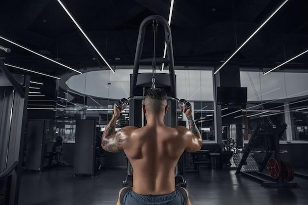 Kalmte. jonge gespierde blanke atleet oefenen in de sportschool met de gewichten. mannelijk model dat krachtoefeningen doet, zijn bovenlichaam traint. wellness, gezonde levensstijl, bodybuilding concept.