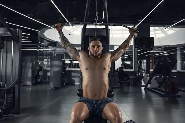 Kalmte. jonge gespierde kaukasische atleet oefenen in de sportschool met de gewichten. mannelijk model krachtoefeningen doen, zijn bovenlichaam trainen. wellness, gezonde levensstijl, bodybuilding-concept.
