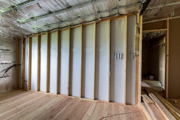 Kamer in aanbouw en renovatie met zilverkleurige aluminiumfolie op muren en plafond, eiken vloer en houten houten frame voor toekomstige scheidingsmuur. professioneel reconstructie- en isolatieconcept.