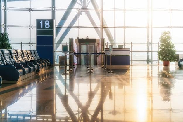 Kamerhoge glazen ramen en ligstoelen in de luchthaventer