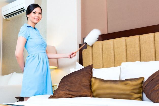 Kamermeisje afstoffen in aziatische hotelkamer