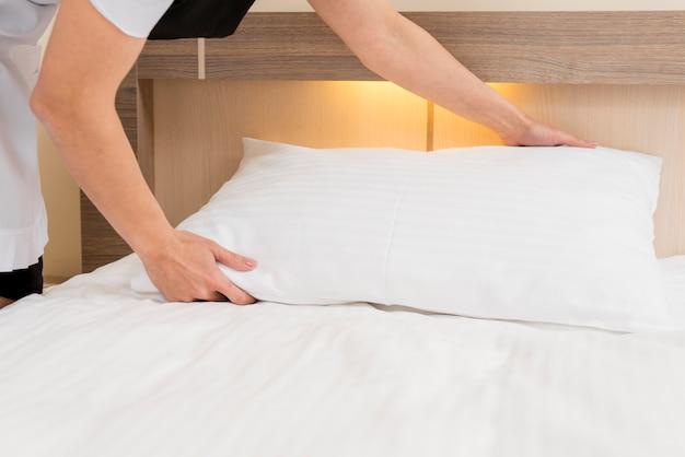 Kamermeisje die hotelkamer voorbereiden