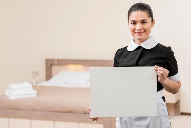Kamermeisje in hotelkamer met laptop