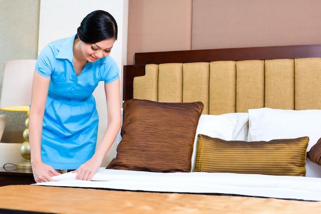 Kamermeisje maken bed in aziatische hotelkamer