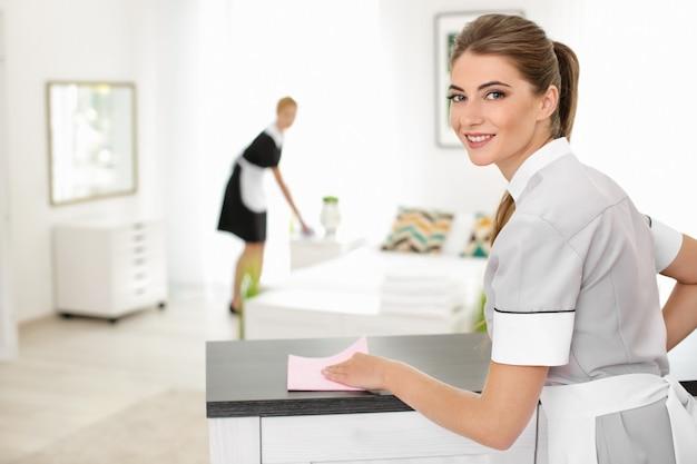 Kamermeisje schoonmaaktafel van stof in de kamer