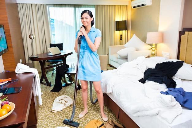 Kamermeisje schoonmaken in aziatische hotelkamer