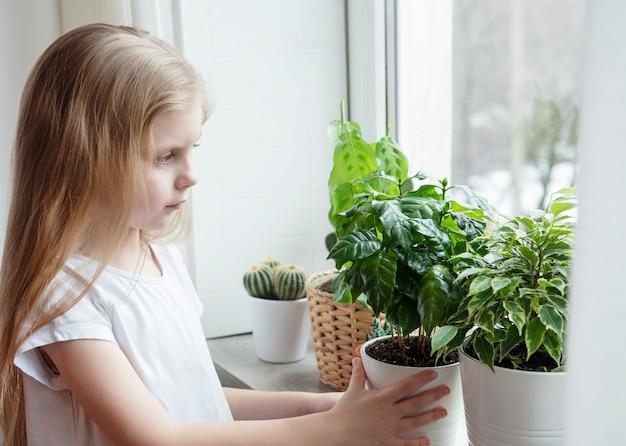 Kamerplant zorg, kleine meisje zorg voor kamerplanten