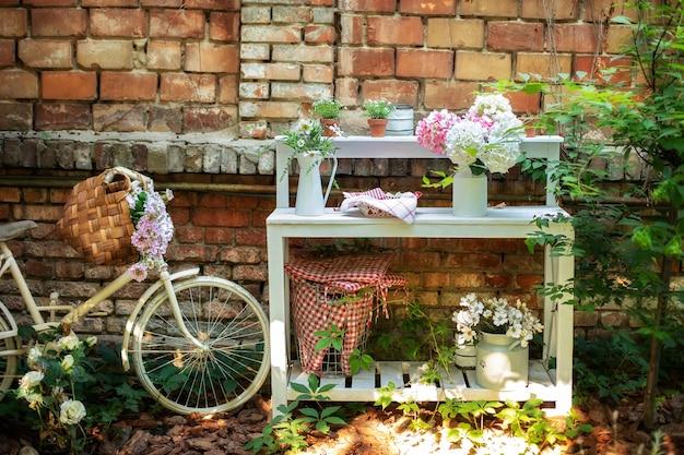 Kamerplanten in potten op tafel tegen bakstenen muur op terras decoratieve fiets in tuin