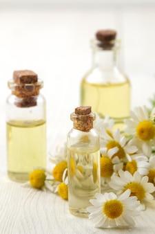 Kamille. medicinale kleine bloemen van kamille met aroma-oliën op een witte houten tafel. detailopname