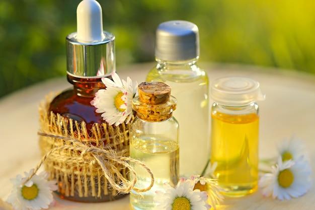 Kamille olie. set etherische olie van kamille in flessen op een ronde houten bord in het gras. biologische veganistische natuurlijke cosmetica