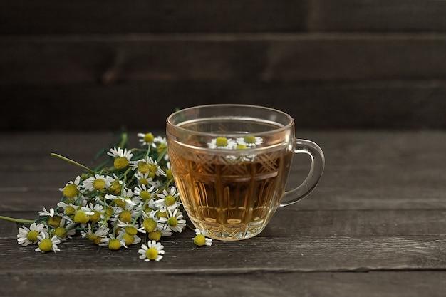 Kamille thee. ernaast staat een boeket veldmadeliefjes.
