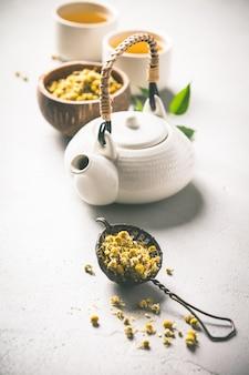 Kamille thee in zeef op vintage achtergrond
