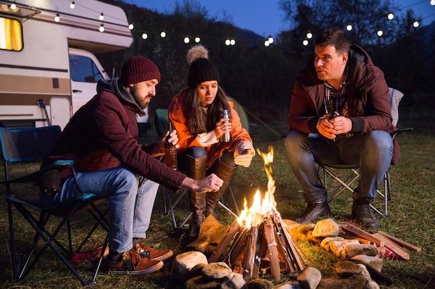 Kampeerders ontspannen samen rond het kampvuur en drinken bier. retro kampeerauto op de achtergrond.