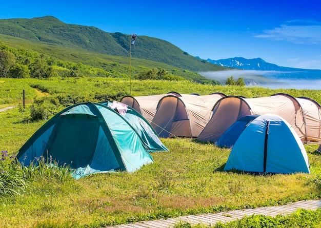 Kampeertent op camping in nationaal park. toeristen kampeerden in het bos aan de oever van het meer op de heuvel.