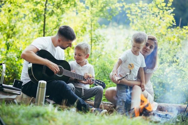 Kamperen aan een meer in het bos. gelukkige familie vader moeder en kleine kinderen zitten bij vuur en tent in de natuur. samen vrije tijd doorbrengen op vakantie. buitenshuis. ouders met kinderen. vader gitaar spelen. kamp