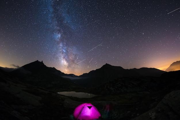 Kamperen onder de sterrenhemel en melkweg op grote hoogte in de alpen.