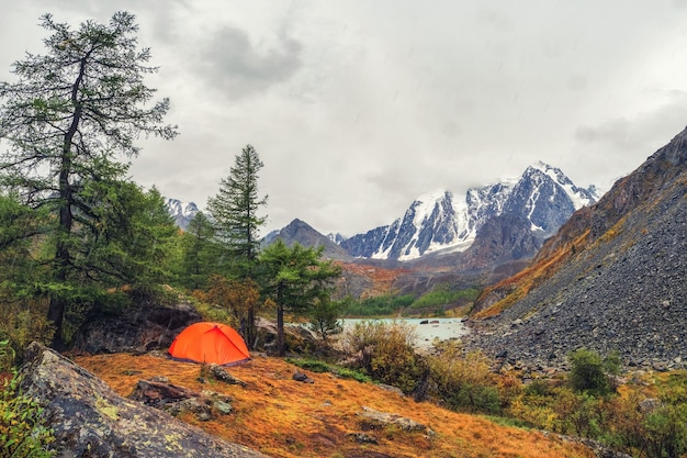 Kamperen op een hooggelegen herfstplateau. oranje tent onder de regen. rust en ontspanning in de natuur. hoger shavlin-meer in de altai.