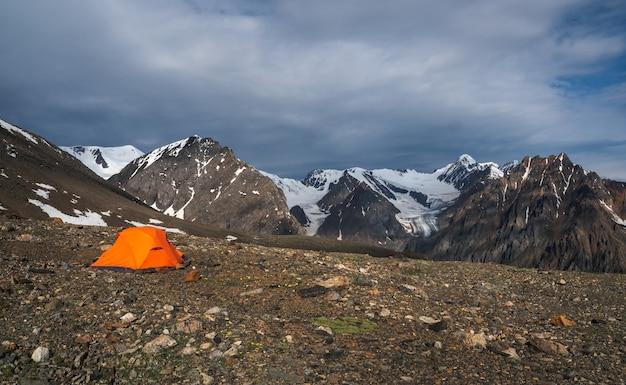 Kamperen op een rotsachtig hooggelegen plateau. oranje tent op de achtergrond van hoge besneeuwde bergen. panoramisch zicht.