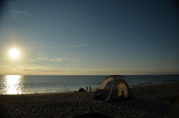 Kamperen op het strand bij zonsondergang