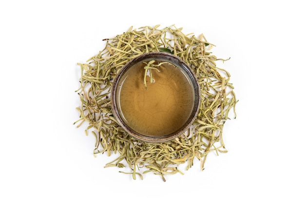 Kamperfoeliebloem en thee op witte oppervlakte wordt geïsoleerd die. bovenaanzicht, plat leggen