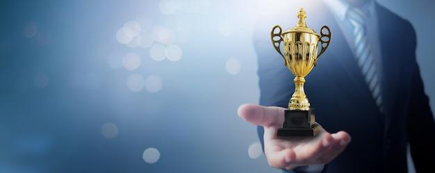 Kampioen en succeswinnaarconcept, de kop van de zakenmanholding van leiderschapstrofee en kampioen van zaken op zacht blauw en bokeh
