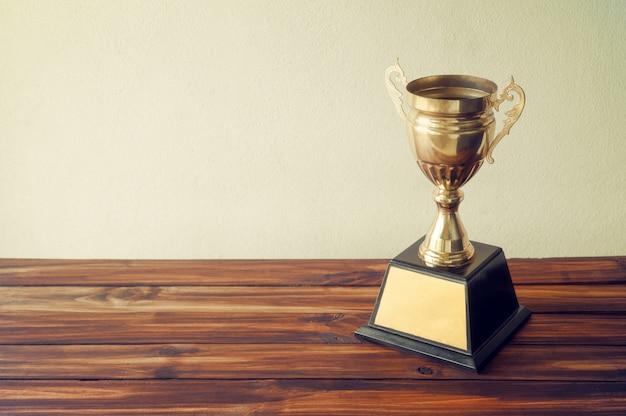 Kampioen gouden trofee op houten tafel met kopie ruimte klaar voor uw ontwerp.