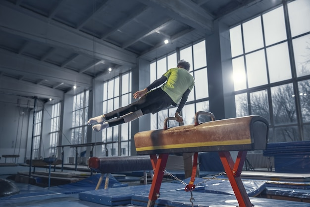 Kampioen. kleine mannelijke turnster training in de sportschool, flexibel en actief