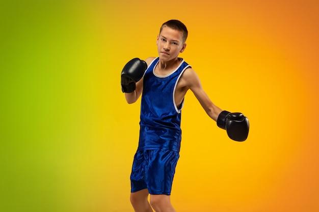 Kampioen. tiener professionele bokser training in actie, beweging geïsoleerd op verloop achtergrond in neonlicht. schoppen, boksen. concept van sport, beweging, energie en dynamische, gezonde levensstijl.
