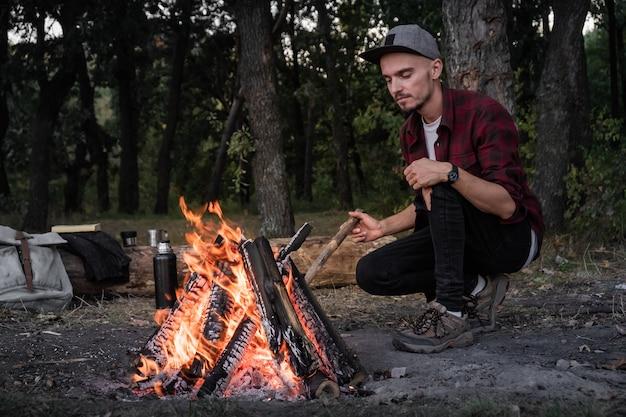 Kampvuur maken bij een bos. going into the wild concept: kampeerplaats met vintage rugzak, thermoskan en man in vrijetijdskleding legt stukken hout in brand.