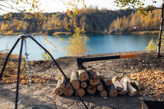 Kampvuur met houten stammen en bijl