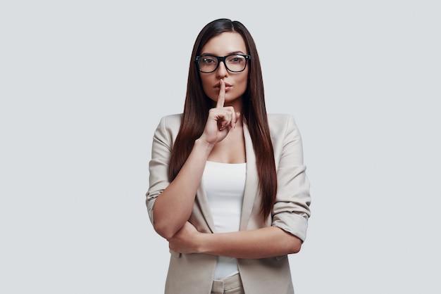 Kan je een geheim bewaren? aantrekkelijke jonge vrouw die naar de camera kijkt en de vinger op de lippen houdt terwijl ze tegen een grijze achtergrond staat