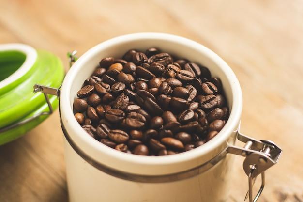 Kan met korrels van koffie op een houten tafel.