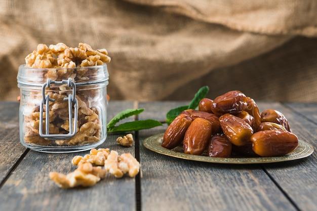 Kan met noten dichtbij plantentakje en gedroogd fruit op lijst