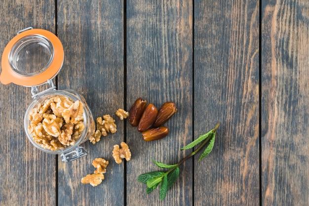 Kan met noten in de buurt van plantentakje en gedroogd fruit