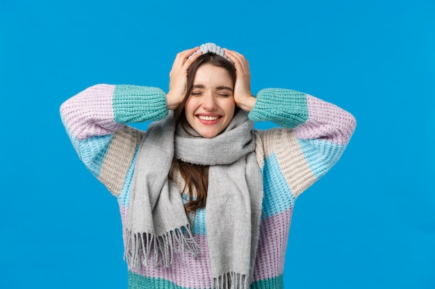 Kan niet geloven dat dromen uitkomen, kerstwonder, nieuwjaarsconcept. aantrekkelijke vrolijke donkerbruine vrouw in de wintersweater, sjaal en jat, dichte dromerige en glimlachende ogen, toejuichend blauw