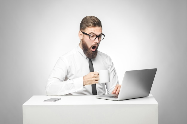 Kan niet geloven! portret van een emotioneel geschokte jonge zakenman in wit overhemd en zwarte stropdas zit op kantoor, leest nieuws en werkt op afstand met verbaasde grote ogen die naar laptop kijken. geïsoleerd