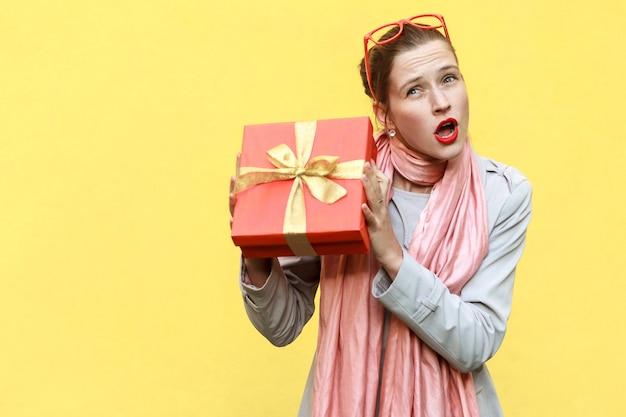 Kan niet staan, het is mijn! speels jong volwassen meisje met geschenkdoos. geïsoleerd op gele achtergrond, studio-opname