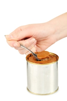 Kan van gekookte gecondenseerde melk met lepel in vrouwelijke hand op wit