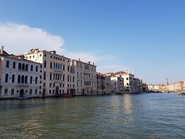 Kanaal in het midden van gebouwen onder een blauwe hemel in italië