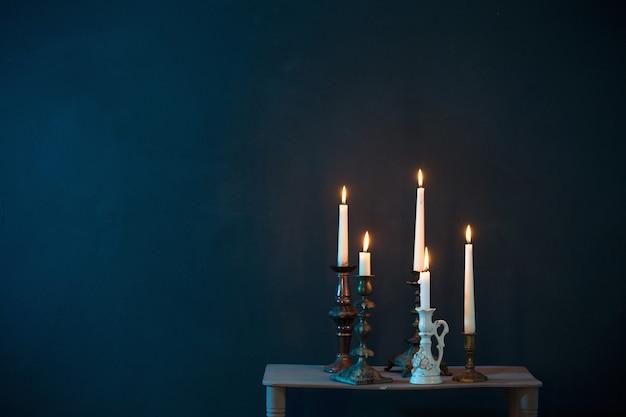 Kandelaars met brandende kaarsen op donkerblauw oppervlak