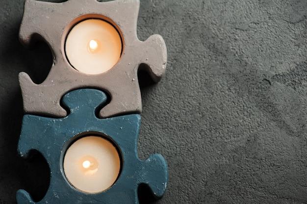 Kandelaars met brandende kaarsen op steenachtergrond