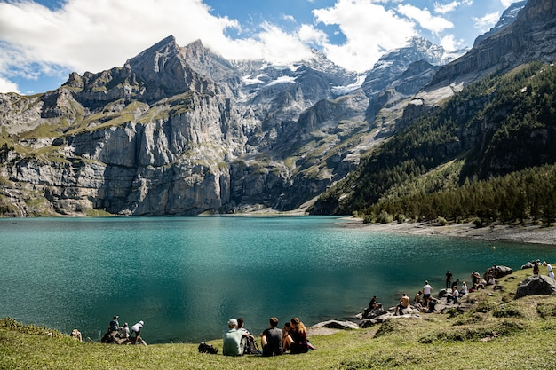 Kandersteg zwitserland - mensen die van de zon genieten bij oeschinesnsee met uitzicht op rothorn, bluemlisalphorn, oechinenhorn, fruendenhorn