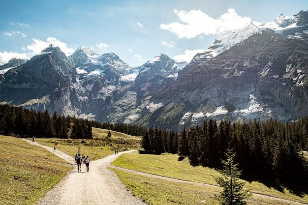 Kandersteg zwitserland - mensen lopen naar oeschinensee met uitzicht op rothorn, bluemlisalphorn, oeschinenhorn, fruendenhorn, doldenhorn