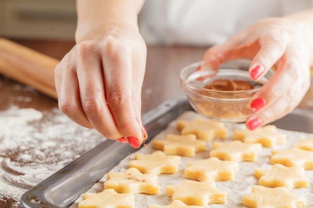 Kaneel bovenop zelfgemaakte koekjes, de laatste stap
