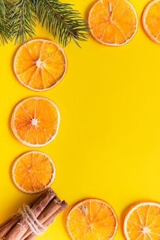 Kaneel, dennentakken, gedroogde sinaasappelfruit en anijs op een geel papier frame.