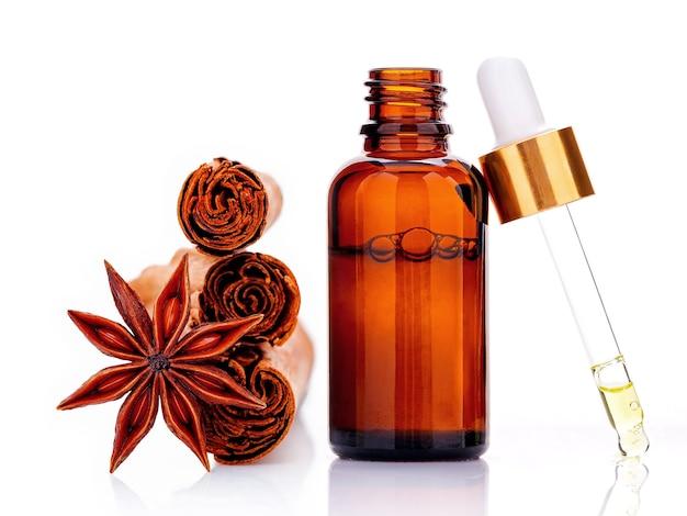 Kaneel etherische olie fles met ceylon kaneelstokjes en anijs ster geïsoleerd op wit.