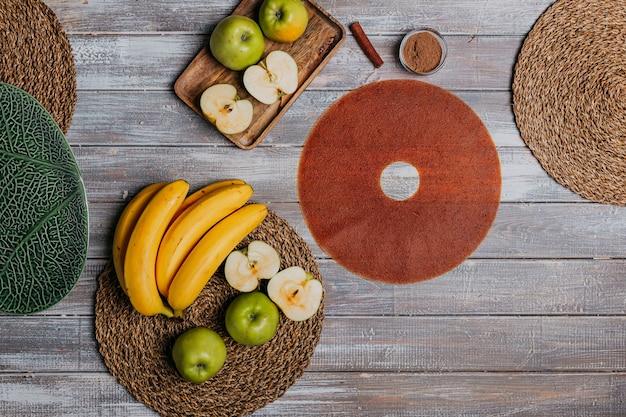 Kaneel fruit leer met vers fruit op de houten tafel. rond fruitleer. gezond eten. appels, bananen en kaneelstokjes bovenaanzicht.