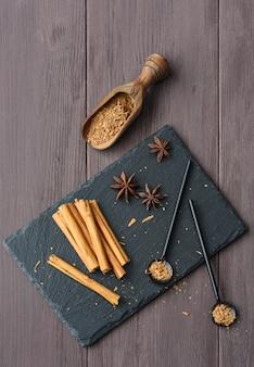 Kaneel stisk en poeder op de houten bruine lijstanijssterren rustieke dichte omhoog kruidig
